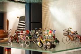 Etwa 15 kleine Blechfahrräder in einem Glasregal