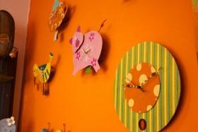 Uhren an einer orangen Wand, die meisten stellen Tiere dar
