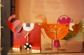 Zwei Uhren, eine als Elefant und eine als Vogel, stehen im Regal