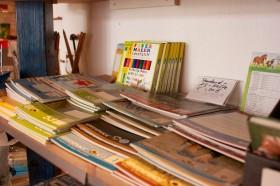 verschiedene Hefte liegen sortiert in einem Regal