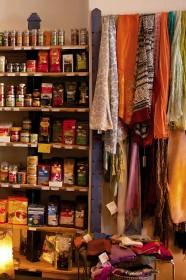 Seidenschals in vielen Farben hängen neben dem Lebensmittel-Regal über einer Stange an der Wand