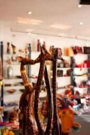 sehr schlanke Giraffenfiguren aus Holz stehen mitten im Laden auf einem Regal