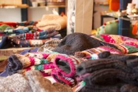 Bunte gestrickte Handschuhe und Mützen liegen im Laden aus